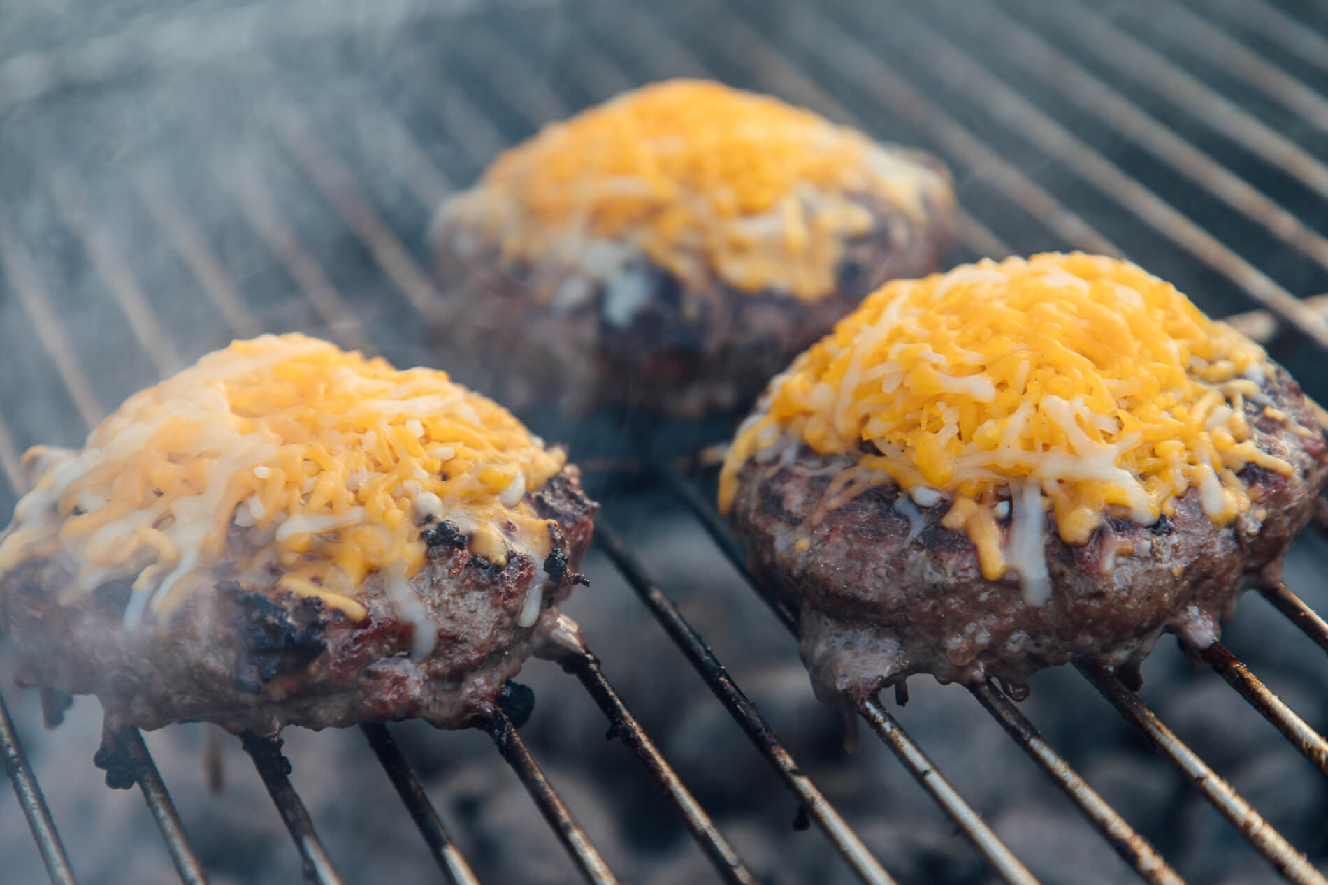 Melting Cheese on Burgers on Grill