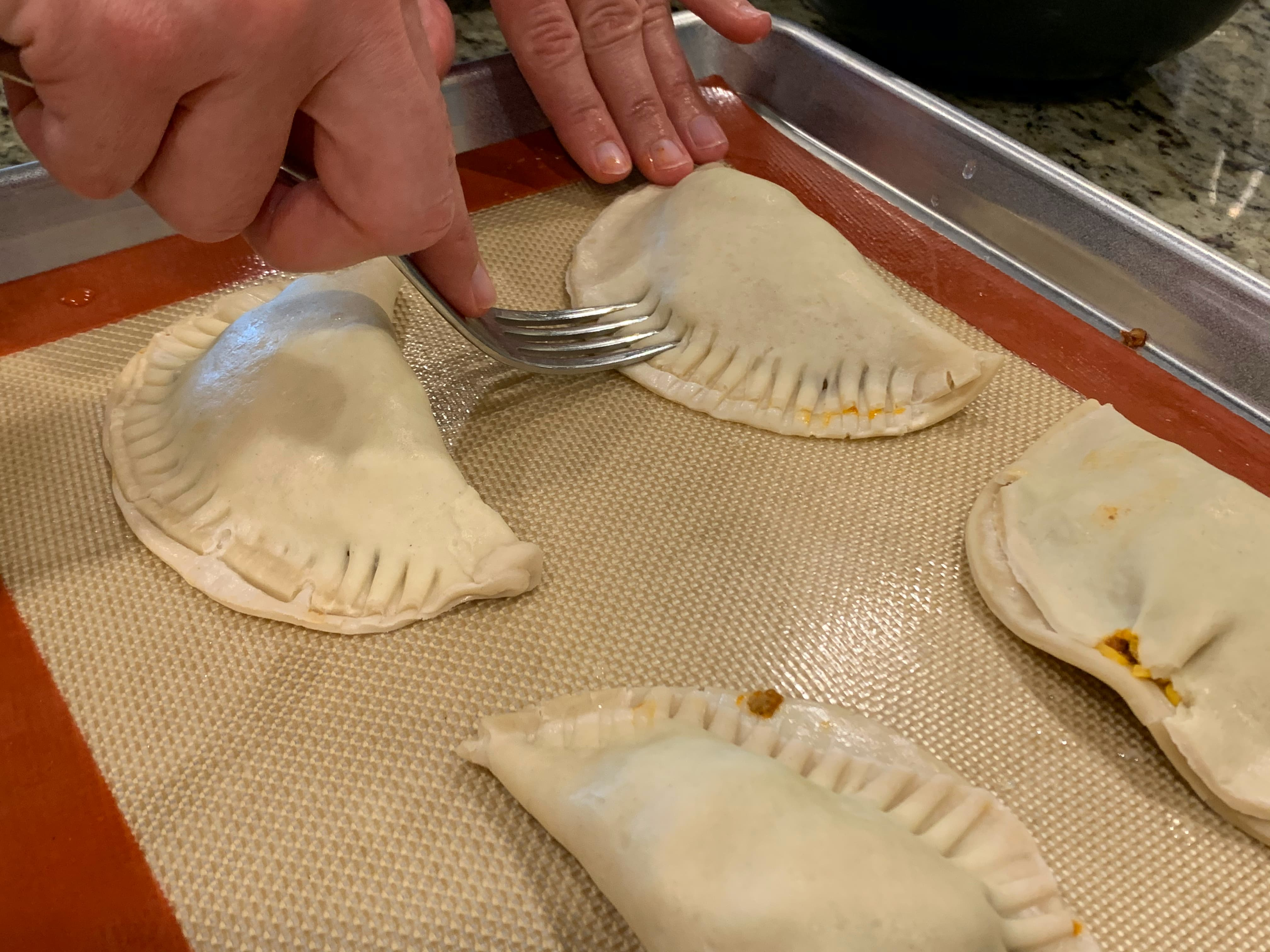 Crimping and sealing empanadas with fork.